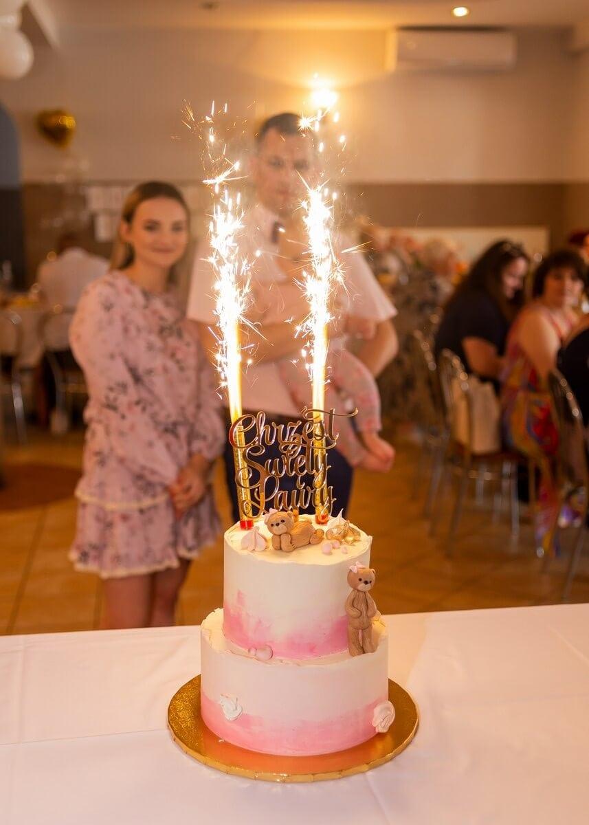 Zdjęcia z chrztu Łódź reportaż z przyjęcia tort z palącymi się świeczkami na tle rodziców z córką L
