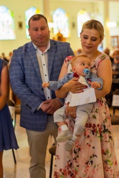 Zdjęcia z chrztu Łódź reportaż z chrztu w kościele rodzice z małym chłopcem i białą szatą SZ15