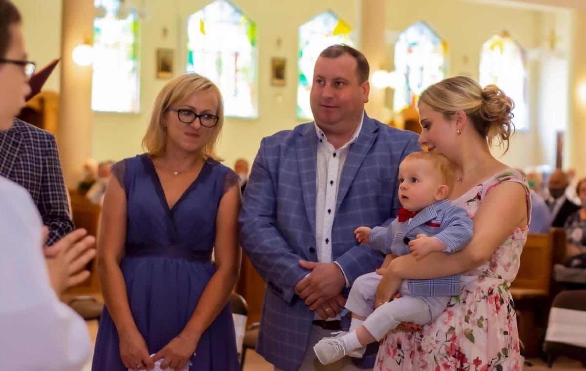 Zdjęcia z chrztu Łódź reportaż z chrztu w kościele mały chłopiec zapatrzony na księdza, a mama chrzestna na chłopca