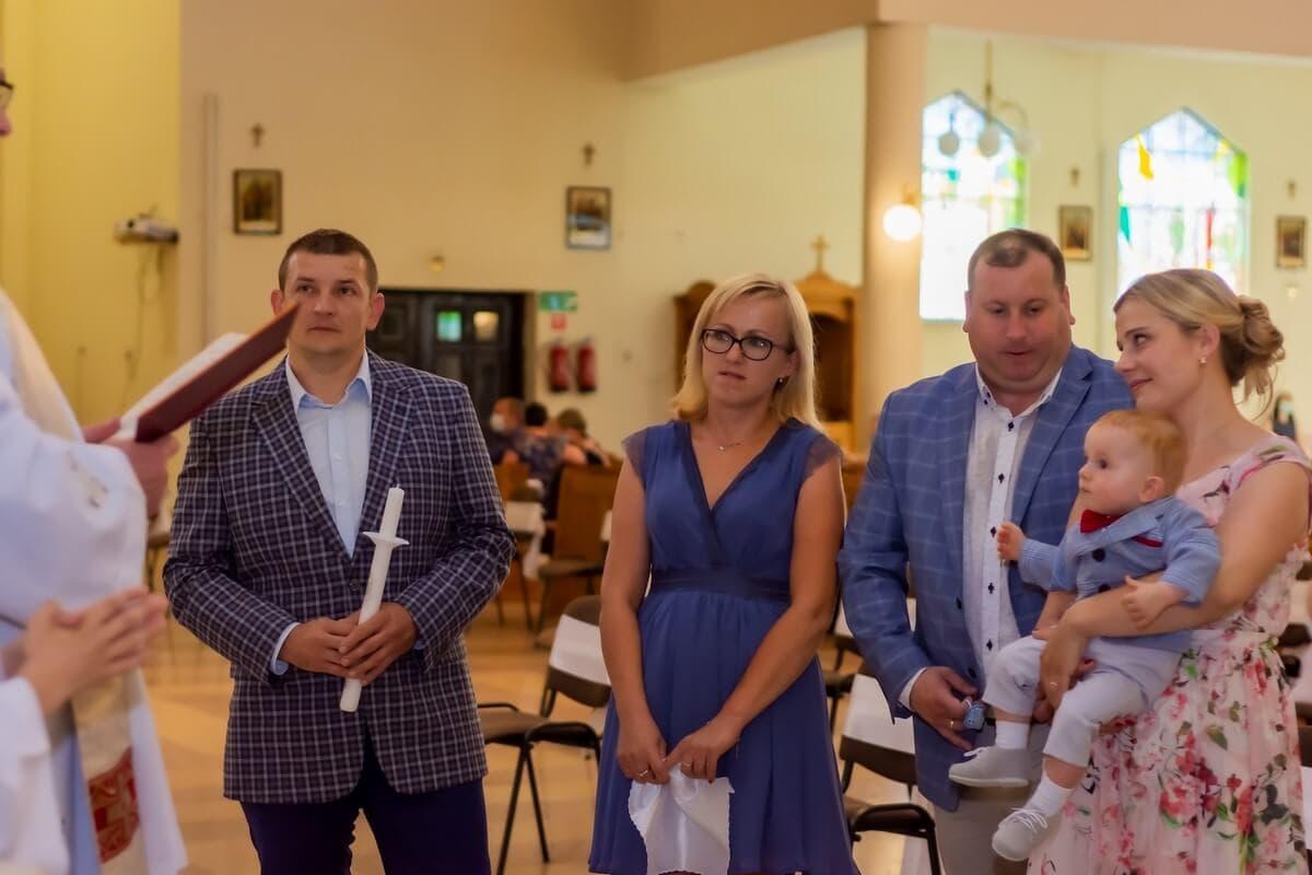 Zdjęcia z chrztu Łódź reportaż z chrztu w kościele rodzice wraz z chrzestnymi stoją i słuchają księdza