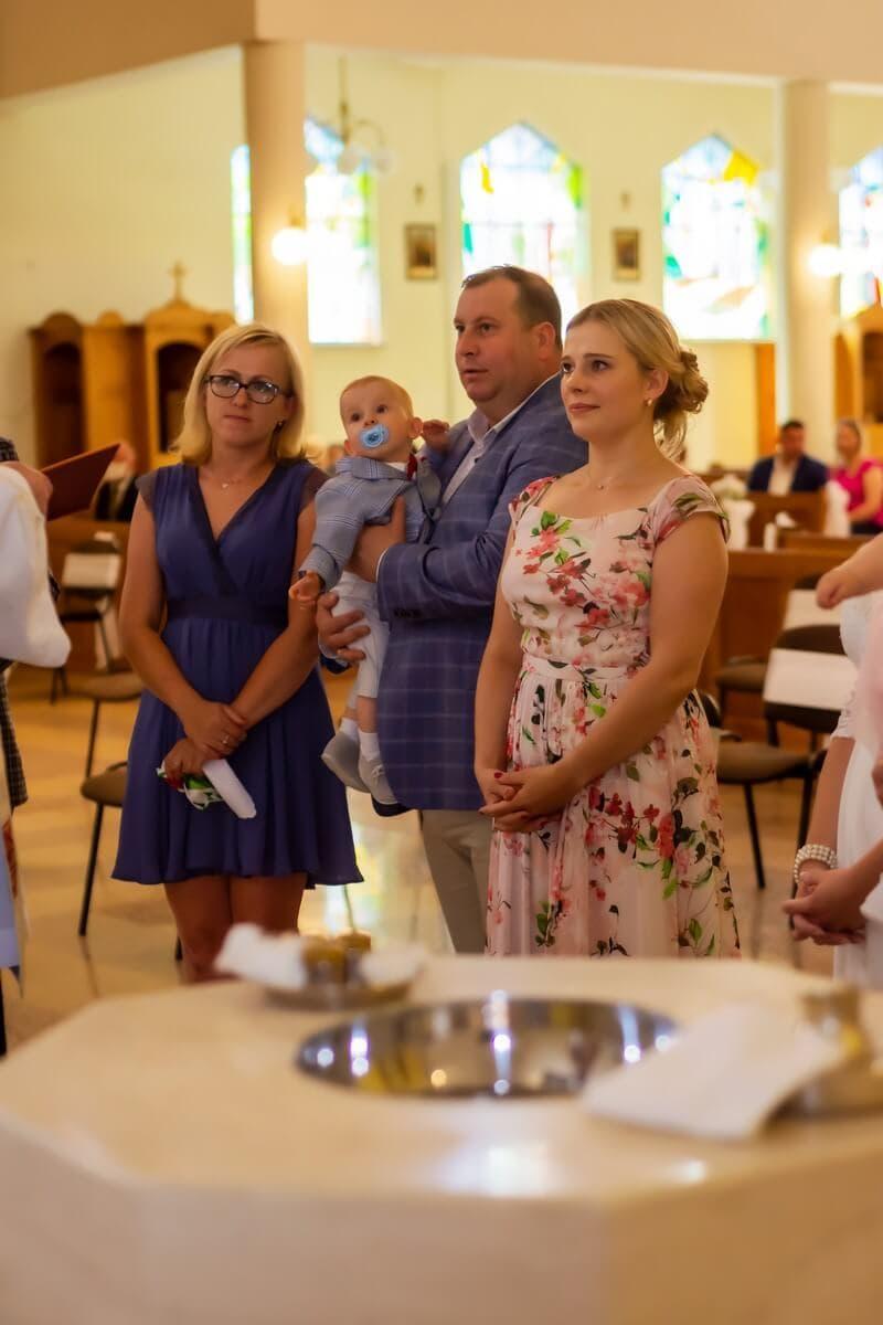 Zdjęcia z chrztu Łódź reportaż z chrztu w kościele rodzice stoją przy chrzcielnicy SZ20