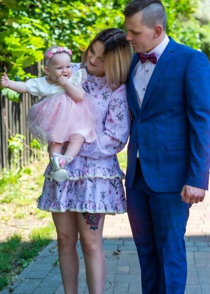Zdjęcia do chrztu Łódź rodzice przy kościele z córką na rękach