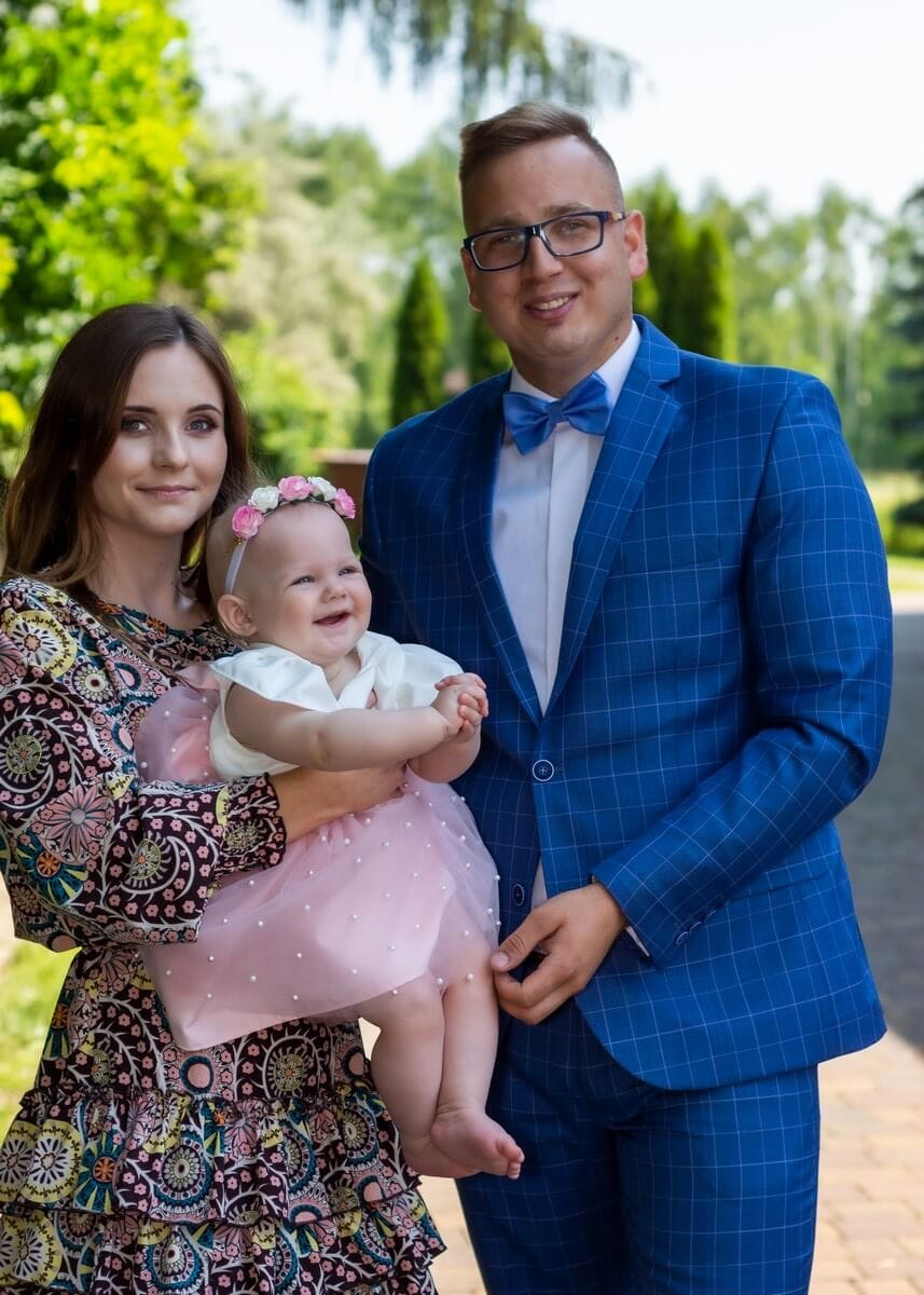 Zdjęcia z chrztu Łódź reportaż z chrztu rodzice chrzestni z dziewczynką przy kościele