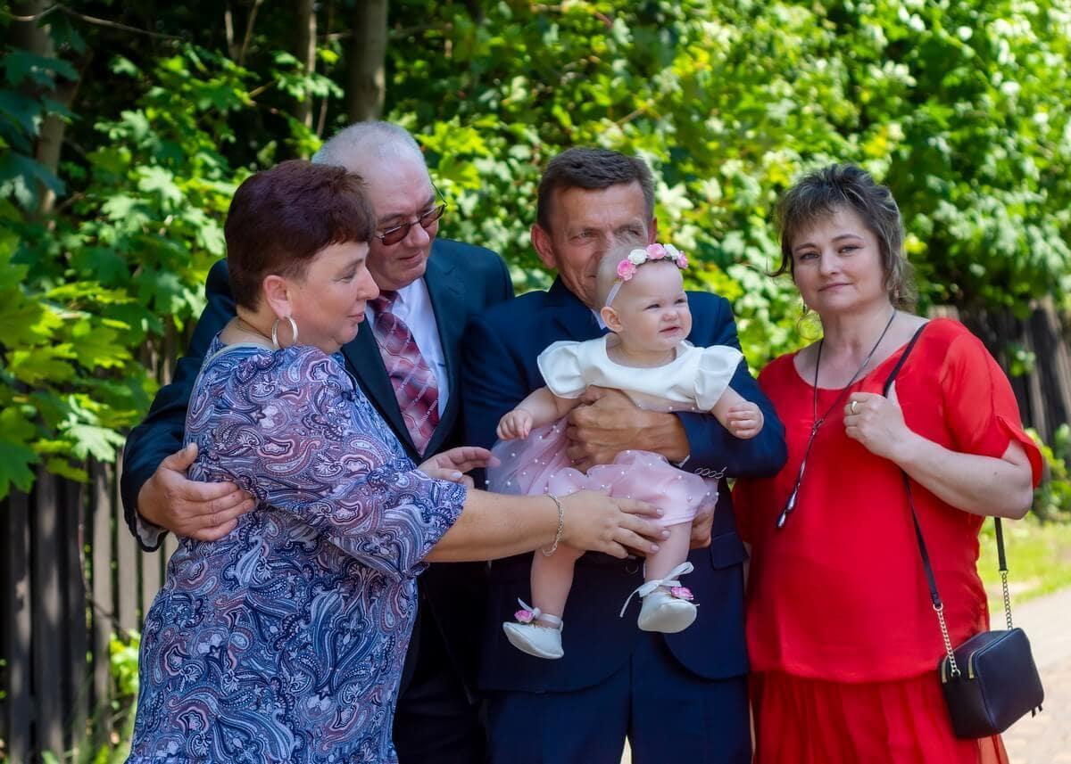 Zdjęcia z chrztu Łódź reportaż dziadkowie z wnuczką na tle drewnianego płotku