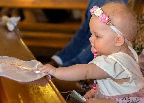Zdjęcia z chrztu Łódź reportaż z chrztu w kościole dziewczynka sięga po białą szatę 19