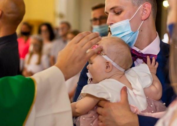 Zdjęcia z chrztu Łódź reportaż ksiądz błogosławi dziewczynkę ze smoczkiem w ustach L23