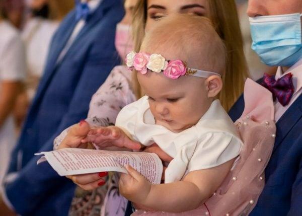 Zdjęcia z chrztu Łódź reportaż z chrztu w kościele Łódź dziewczynka patrzy na tekst pieśni, który ma na kartce w rączkach L01