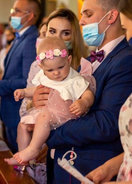 Zdjęcia z chrztu Łódź reportaż z chrztu w kościele dziewczynka na rękach taty patrzy się na kartkę