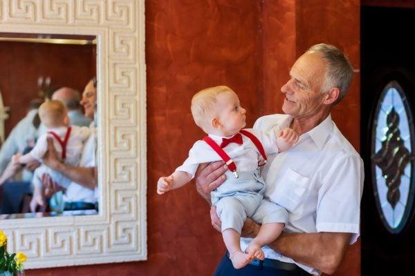 Reportaż z chrztu świętego Łódź dziadek z wnukiem na rękach na tle lustra 15