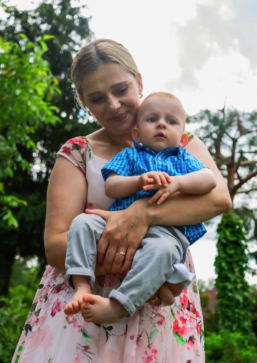 reportaż z chrztu świętego mam z synkiem w ogrodzie na tle nieba