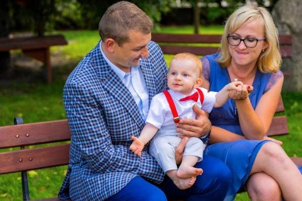 Reportaż z chrztu świętego Łódź para na ławce z chłopcem na kolanach 06