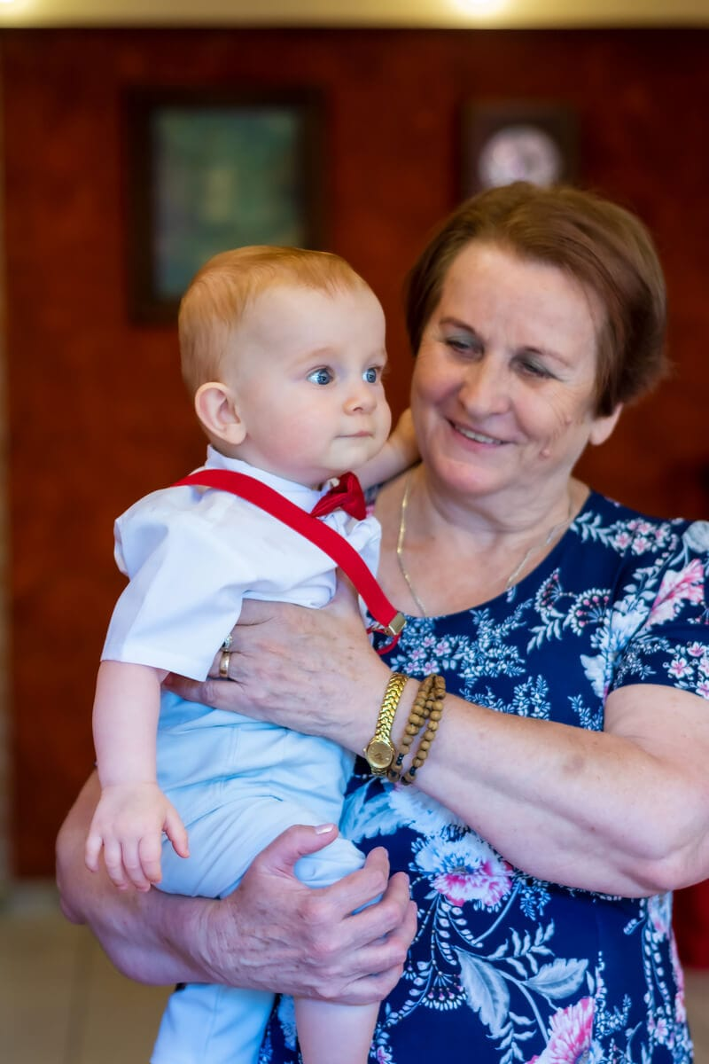 Reportaż z chrztu świętego Łódź babcia uśmiecha się do wnuka na rękach 12