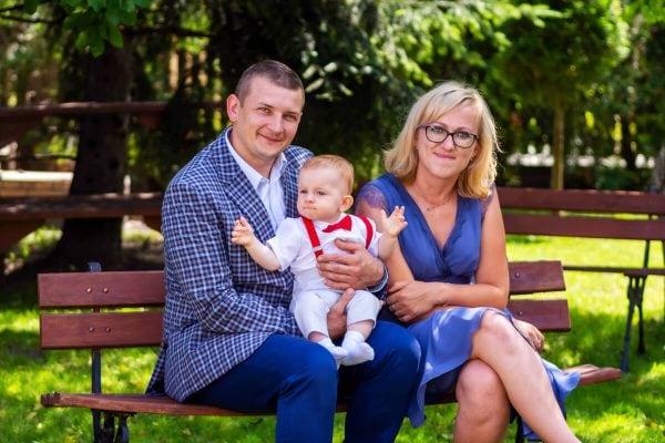 Reportaż z chrztu świętego Łódź para na ławce z małym chłopcem na kolanach 16