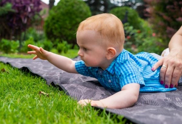 Reportaż z chrztu świętego Łódź chłopiec na kocu na trawie coś chce złapać 3