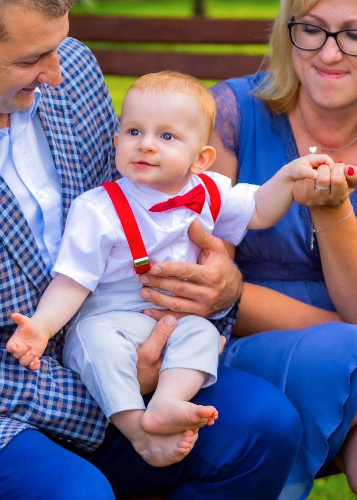 Reportaż z chrztu świętego Łódź chłopiec z czerwoną muchą na kolanch rodzicó 8