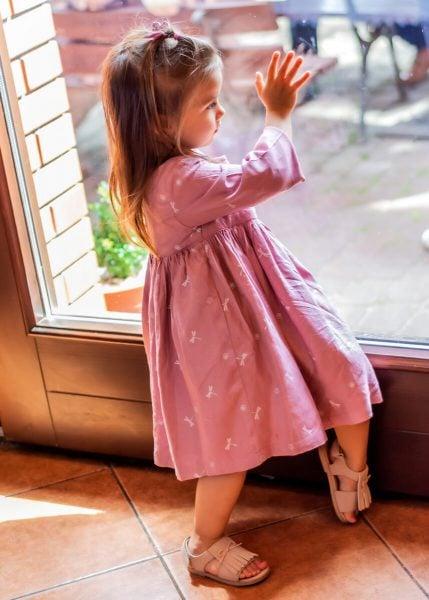 sesja dziecięca łódź reportaż przyjęcie dziewczynka stojąca przy szklanych drzwiach z ręką na szybie