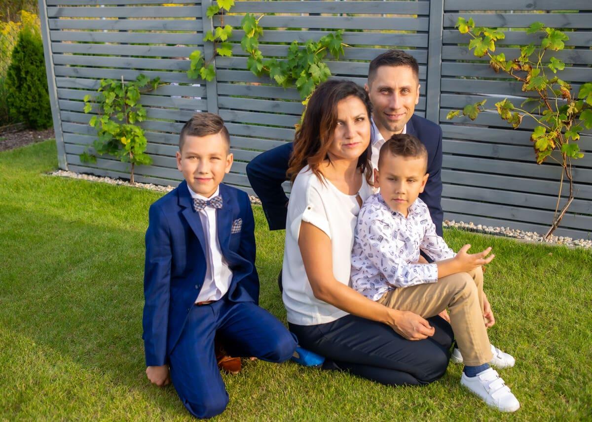 fotografia komunijna łódź lifestyle rodzina siedzi na trawie przy winogronach PHT 05