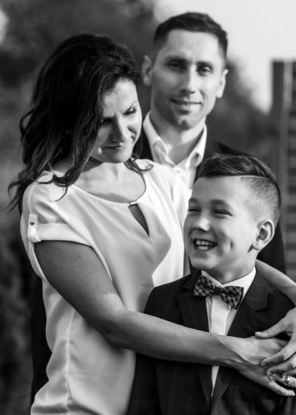fotografia komunijna łódź lifestyle rodzina mama przytula roześmianego chłopca czarno-białe