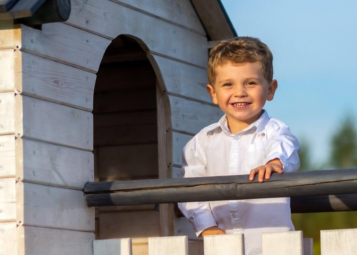 fotografia dziecięca łódź lifestyle chłopiec na drabince stoi na podeście przy domku T3