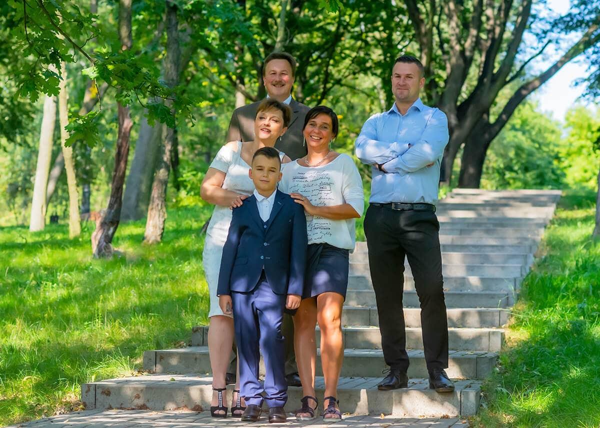 sesja komunijna łódź chłopiec z rodziną stoja na schodach i się cieszą I01