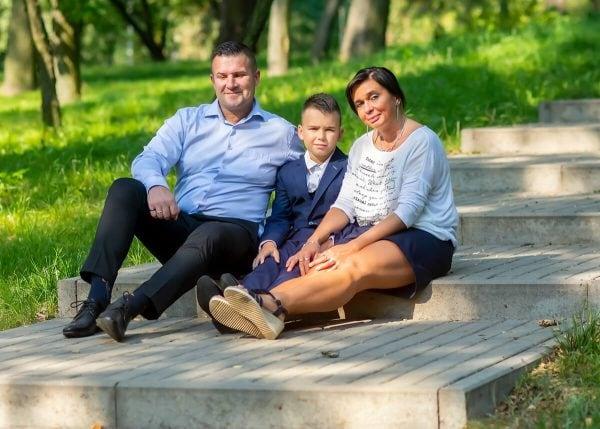 sesja komunijna łódź chłopiec z rodzicami siedzi na schodach I02