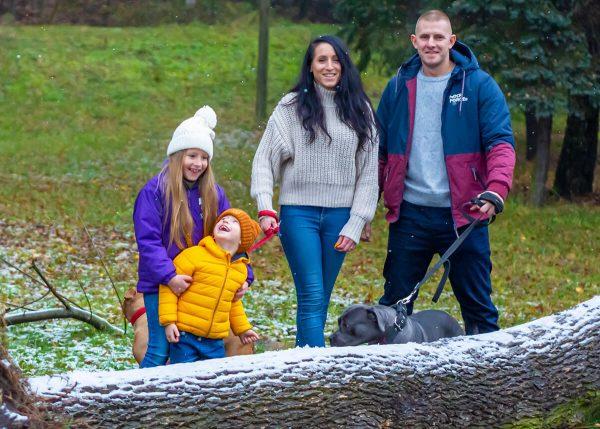 rodzinna sesja zimowa z psami fotograf łódź rodzice z dwójką roześmianych dzieci przy pniu pokrytym śniegiem