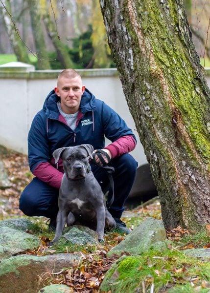 rodzinna sesja zimowa z psami fotograf psów łódź mężczyzna kuca z psem przy drzewie