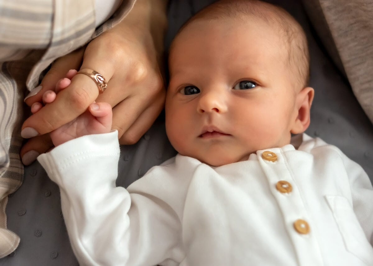 naturalna fotografia noworodkowa Łódź noworodek leży na plecach i trzyma mamę za palec