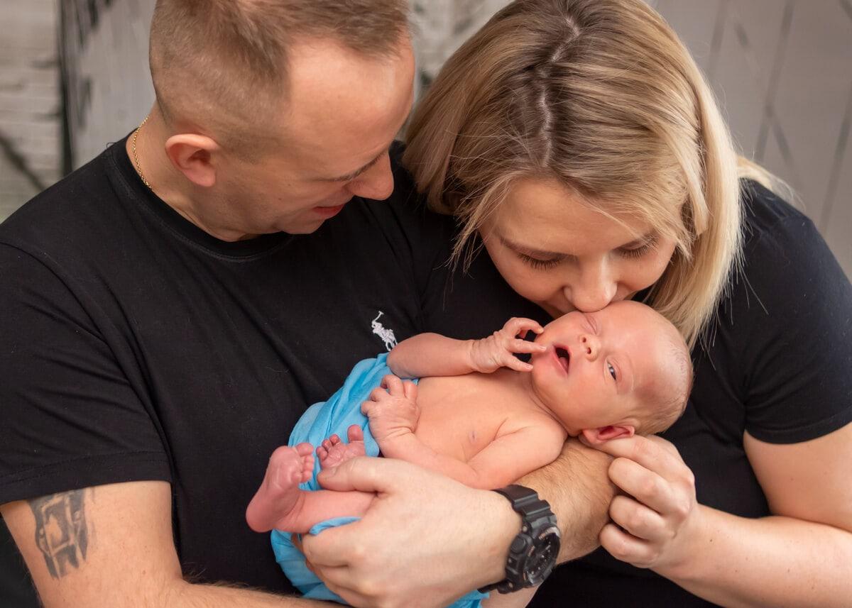 sesja noworodkowa w domu łódż noworodek w ramionach taty mama całuje go w głowę
