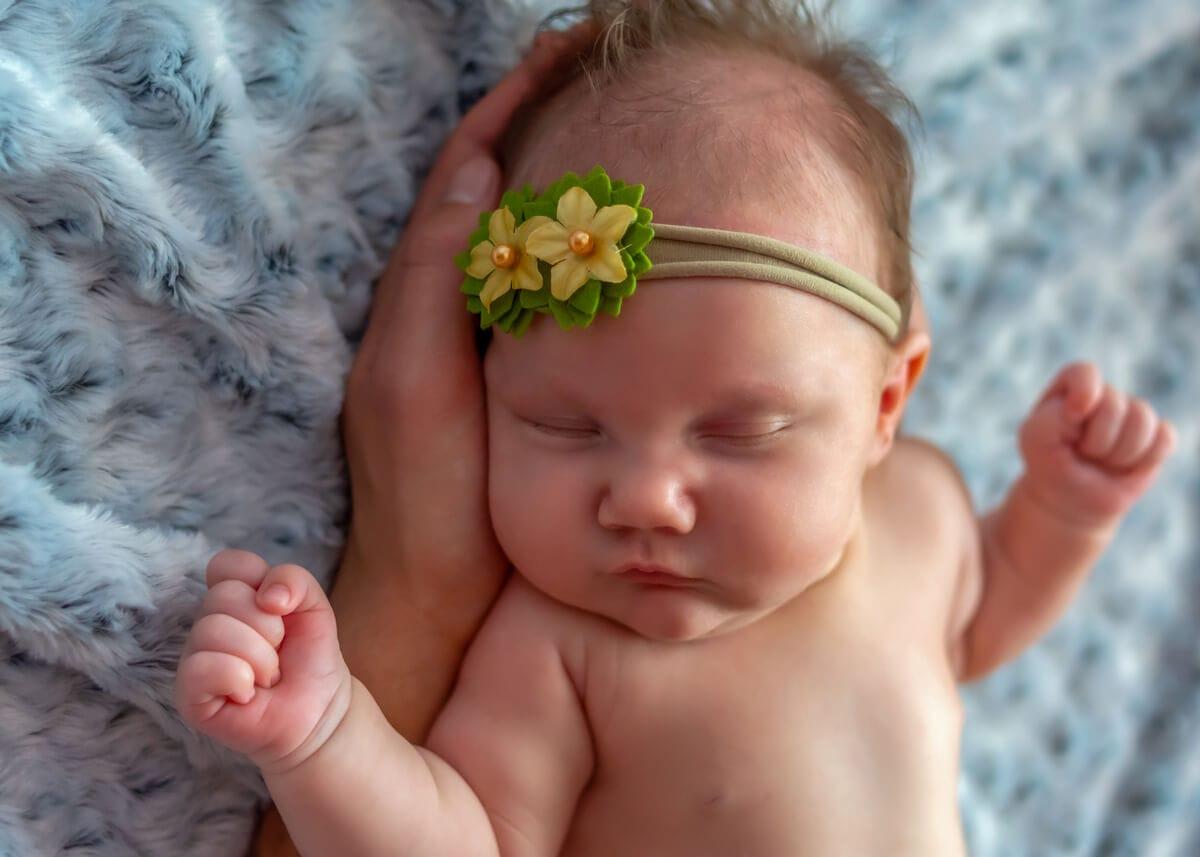 sesja rodzinna z noworodkiem łódź dziewczynka śpiąca na dłoni taty z rozłożonymi rączkami