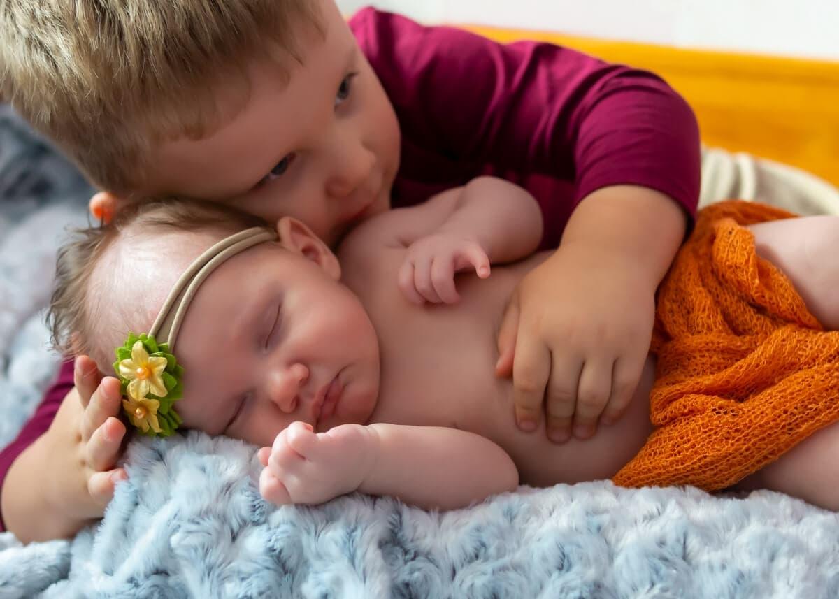 sesja rodzinna z noworodkiem łódź starszy brat przytula śpiącą siostrę noworodka