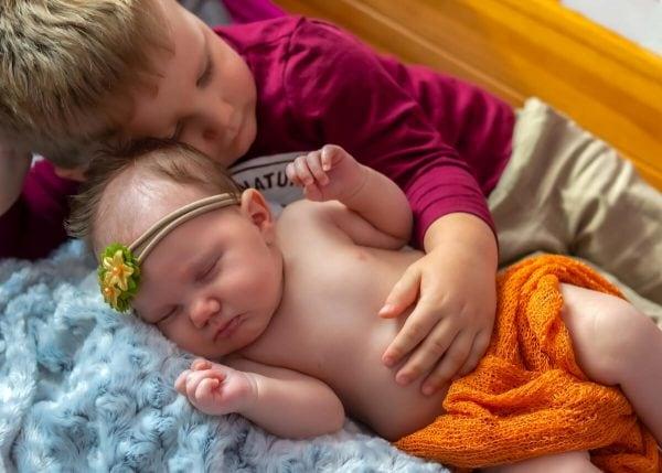 sesja rodzinna z noworodkiem łódź brat przytula się do młodszej śpiącej siostry