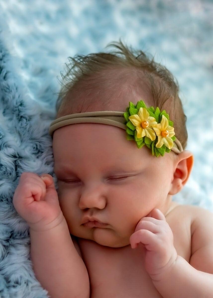sesja rodzinna z noworodkiem łódź śpiąca dziewczynka podpiera ręką brodę