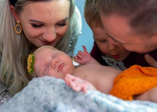 sesja rodzinna z noworodkiem łódź rodzice wraz z synem nachylają się nad śpiącą dziewczynką noworodkiem