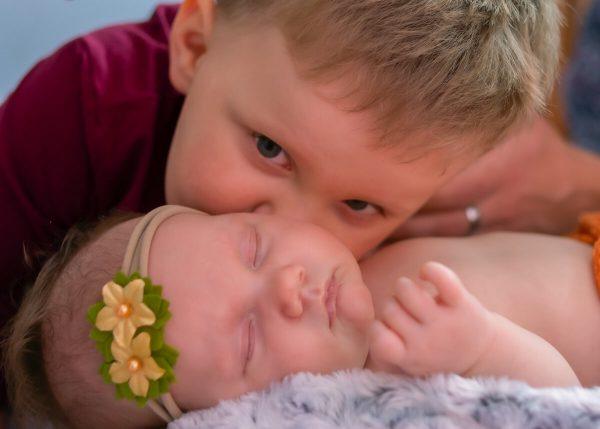 sesja rodzinna z noworodkiem łódź chłopiec całuje śpiącą siostrzyczkę noworodka