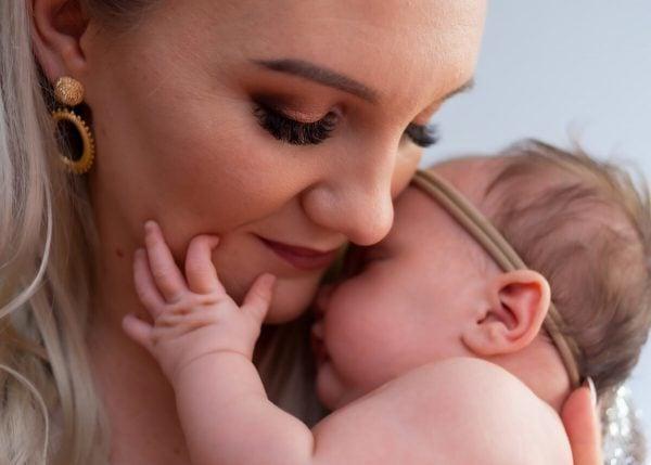 sesja rodzinna z noworodkiem łódź noworodek wtulony w mamę trzyma rączkę na jej policzku