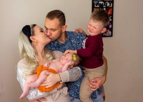 sesja rodzinna z noworodkiem łódź mama z noworodkiem na rękach całuje tatę z synkiem na rękach