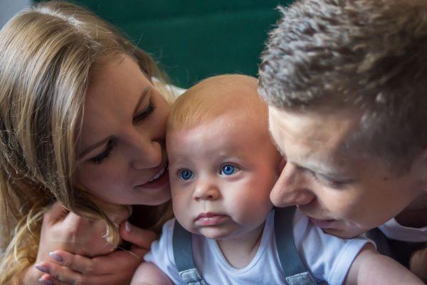 naturalna rodzinna sesja niemowlęca łódź rodzice z dzieckiem na łóżku blisko siebie