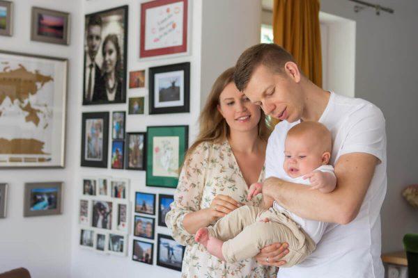 naturalna rodzinna sesja niemowlęca łódź w domu rodzice bujają dziecko